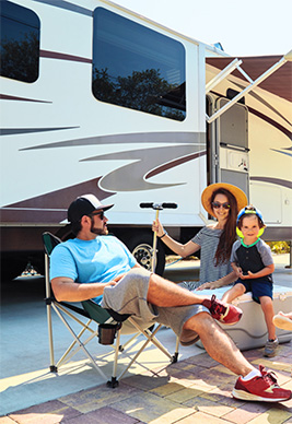 family sitting next to rv rental